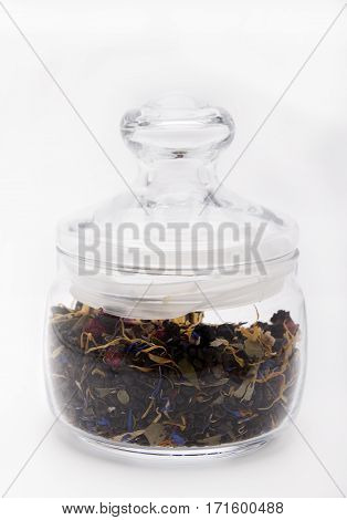 Picking of green tea with herbs and berries in a jar of glass