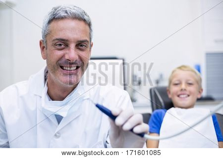 Portrait of smiling dentist holding dental tool in dental clinic