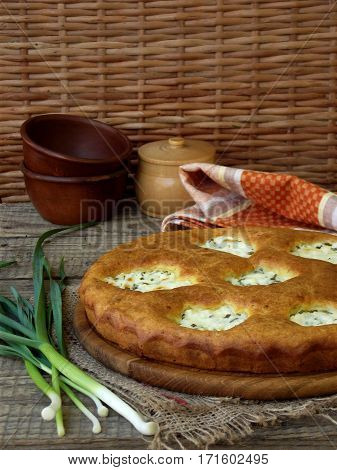Salted Pie With Cottage Cheese And Young Green Garlic On A Wooden Background