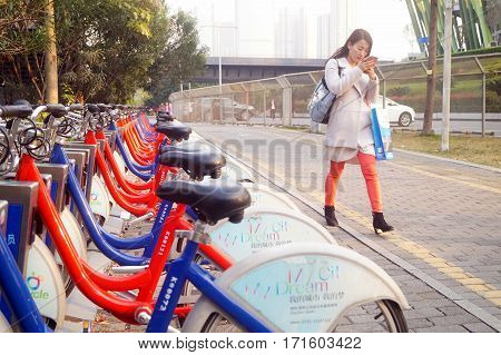 Shenzhen, China: a young woman walks past a bicycle rental facility in February 11th, 2017. In Shenzhen, china.