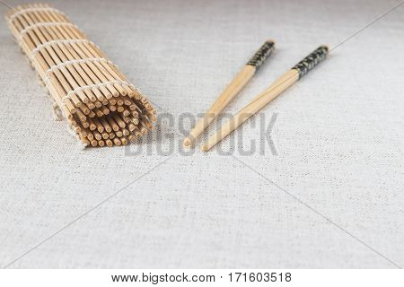 Wooden sushi chopsticks with rolled bamboo straw mat space for text