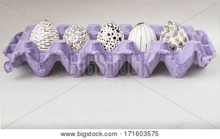 Decorating Easter eggs using a traditional wax-resist method and modern patterns. Eggs in a purple paper box with molten wax applied to the white shell