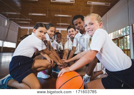 Portrait of sports teacher and school kids forming hand stack in basketball court at school gym