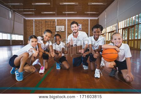 Portrait of sports teacher and school kids showing thumbs up in basketball court at school gym