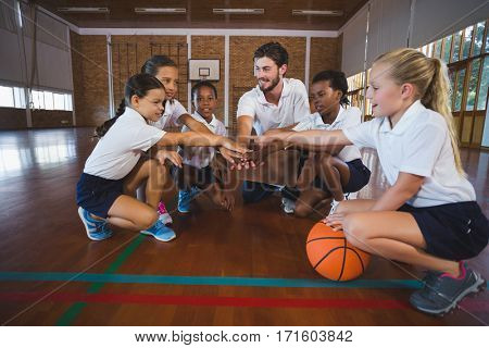 Sports teacher and school kids forming hand stack in basketball court at school gym