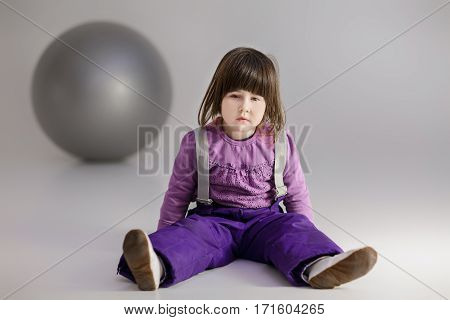 little cute girl in purple clothes with a large ball for fitness on  gray background.