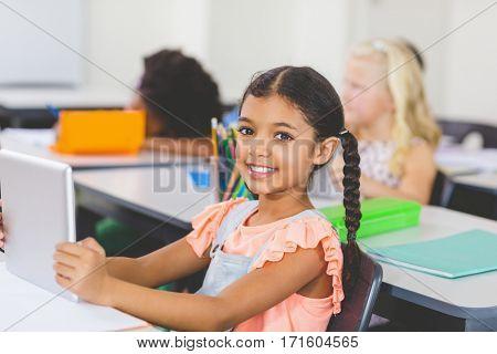Portrait of schoolgirl using digital tablet in classroom at school
