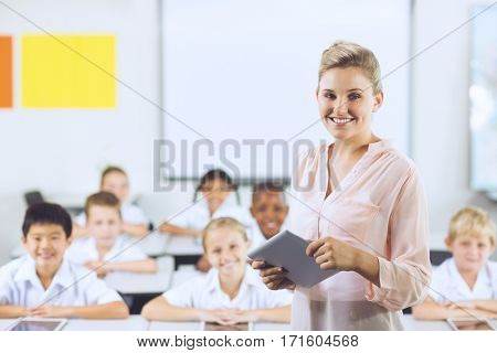Portrait of teacher teaching kids on digital tablet in classroom at school