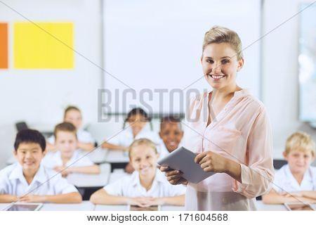 Portrait of teacher teaching kids on digital tablet in classroom at school