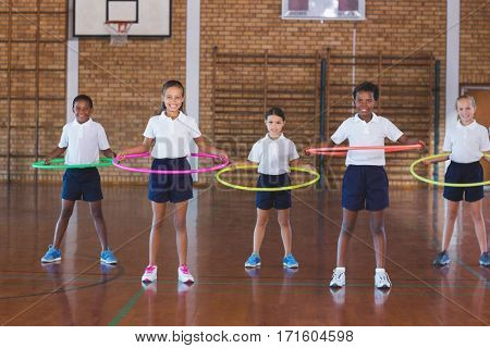 School kids playing with hula hoop in basketball court at school gym