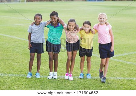 Portrait of school kids standing with arms around in playground