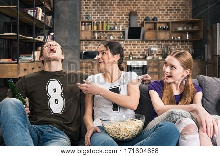 Happy young friends sitting on sofa and eating popcorn from glass bowl