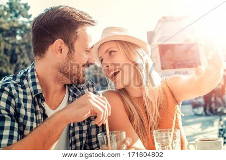 Happy young couple taking selfie with smart phone at cafehaving fun.