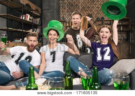 Excited young friends in hats cheering and drinking beer at st patricks day