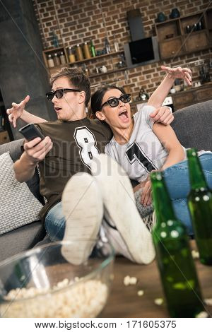 portrait of frightened woman and man in 3D glasses looking away while watching movie