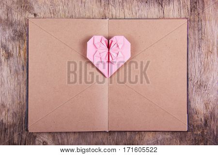 Heart origami and book with blank pages. Pink heart made of paper and diary. Copy space