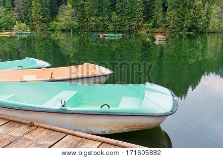 Boats at wooden relaxing area on the sovata lake in romania, rest area surrounded by historic forested mountains, rainy day, fog and reflection, near salt mine