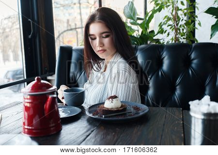technologies emotions lifestyle people teens concept -Young happy female reading on her mobile phone while sitting in modern coffee shop interior gorgeous hipster girl with beautiful smile