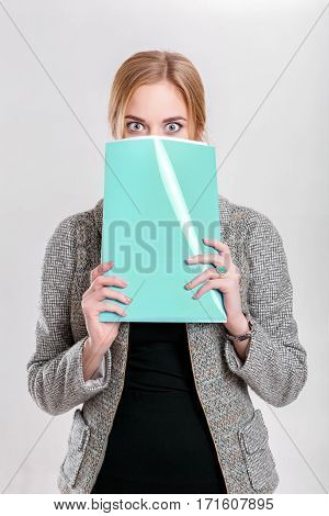 young beautiful business woman blonde in black dress, jacket covers his face with a folder of papers and wonders on gray background