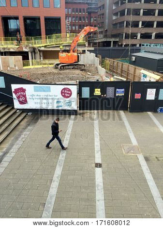 Reading, England - February 16, 2017: A pedestrian passes by a construction site in Reading, England where extensive regeneration of the town centre is taking place