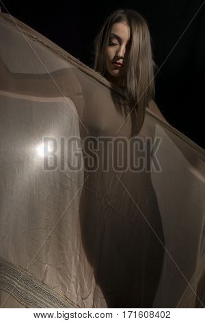 Naked woman wearing around her body a thin shawl