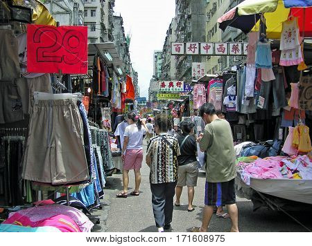 Mong Kok, Hong Kong - March 23, 2003: People strolling through a street market in Mong Kok for shopping.