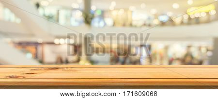 Wooden board empty table blurred background. Perspective brown wood table over blur in department store background Panoramic banner - can be used mock up for montage products display or design.