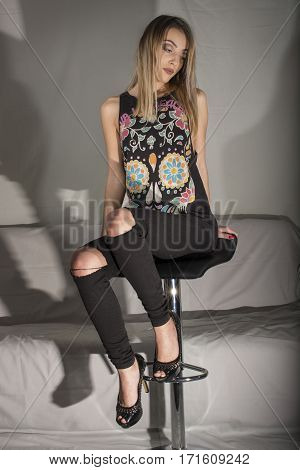 Blond girl with black top and jeans sitting on chair