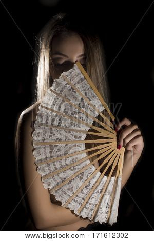 Shy woman hiding behind lace fan on black background