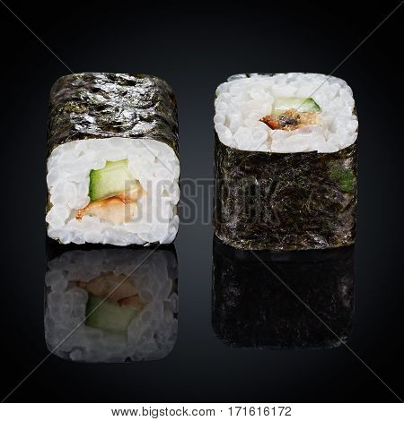 Kappa maki rolls with cucumber and spicy sauce on a black background