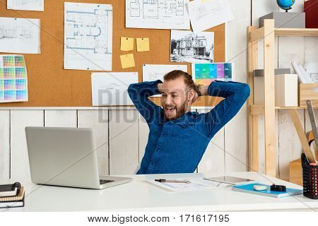 Young successful businessman rejoicing, sitting at workplace with laptop.