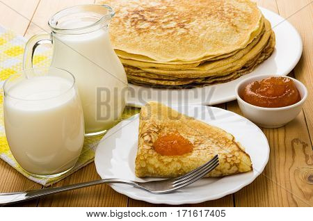 Russian pancakes in dish with peach jam jug milk and glass on wooden table