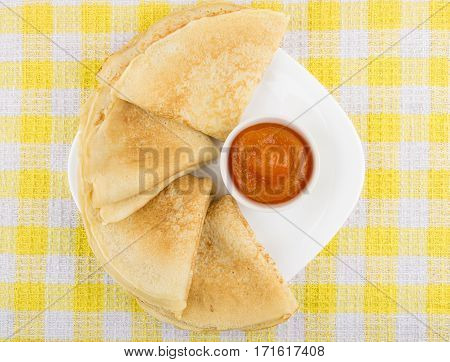 Folded Russian Pancakes In Plate And Bowls With Peach Jam