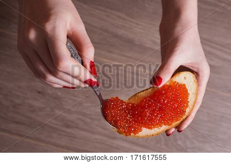 Red caviar close up on a sandwich in a female hand with red nails. Healthy food. Fish appetizer. Russian kitchen. Overlay caviar on bread.