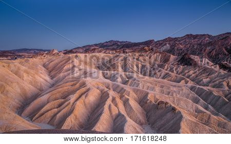 Scenic panoramic view of amazing sandstone formations at famous Zabriskie Point viewpoint in beautiful post sunset twilight Death Valley National Park California USA