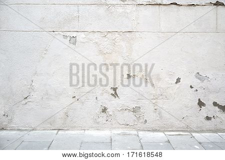 Urban street background. Flaking white wall and grey tiled floor. Copy space for Editor's text.