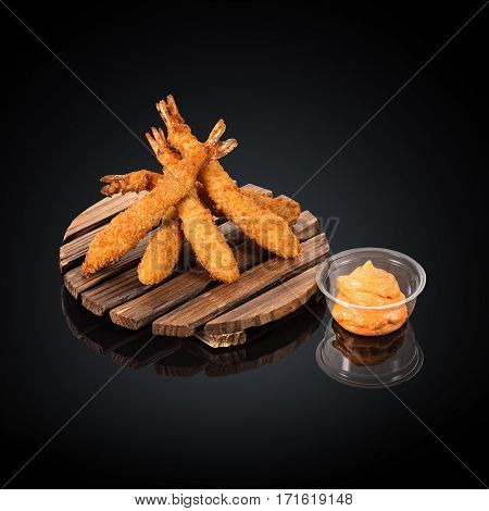 Tiger prawns in batter, spicy sauce on a black background
