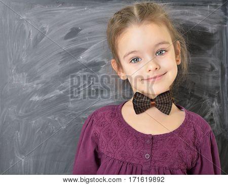 Cute little girl standing near blackboard and happy smiling. Beautiful schoolgirl. Smart pupil girl in classroom.