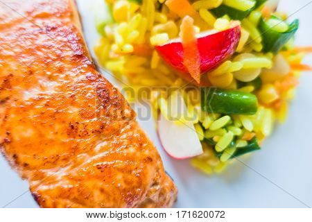 Detail of fried salmon with rice and vegetables