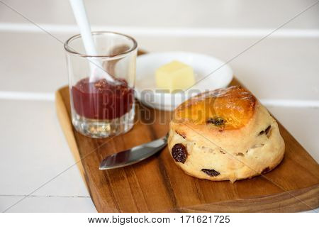 Delicious scone with butter and strawberry jam on wood plate