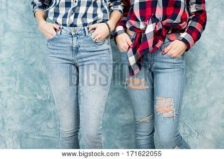 Two female friends in checkered shirts and jeans together on the blue wall background. Close-up view on the legs without face