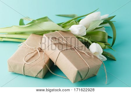 Compliment gift with spring white tulips on plain background