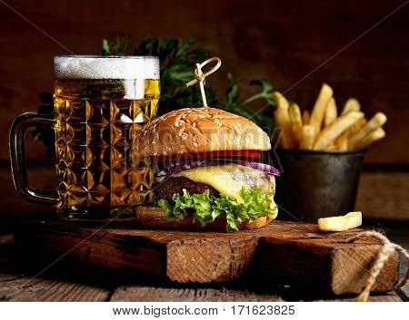 hamburger and mug of beer on wooden table