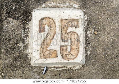the digits with concrete on the sidewalk 25