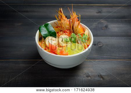 Tom Yum Soup or River Prawn Spicy Sour Soup (Tom Yum Goong) on wooden table Thai local food