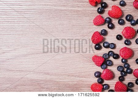 Red ripe raspberry and blueberries lies on a wooden background. Copyspace flat lay top view. Macro