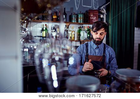 Barista bartender makes coffee at the bar in the restaurant.