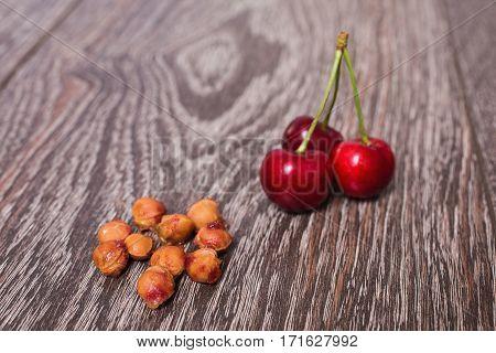 Three red ripe juicy cherries and bones lying on vintage wooden background. Sweet summer berries. Macro photography