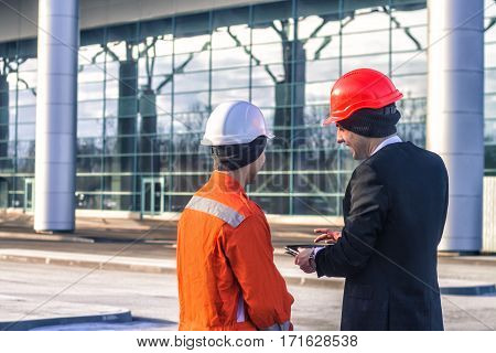young boss and worker in conversation discussing a construction project on tablet. Boss is happy. Business modern background