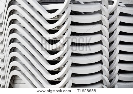 Folded stack of white plastic deck chairs. Pile of beach loungers. Abstract background or texture